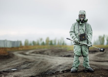 Scientist (radiation supervisor) in protective clothing and gas mask with geiger counter checks the level of radioactive radiation in the danger zone